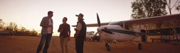 3 guys standing in front of a small airplane and having drinks while having a cheerful conversation. Sunset is at the background.