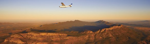Scenic view of a small private airplane flying above Wilpena Pound